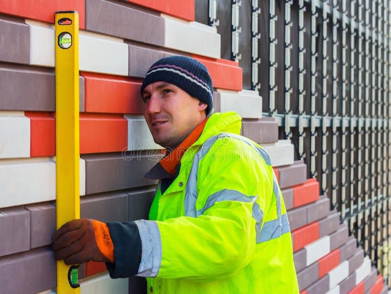 Il costruttore controlla la qualità del lavoro fatto, tenente il livello dell'acqua fotografia stock libera da diritti