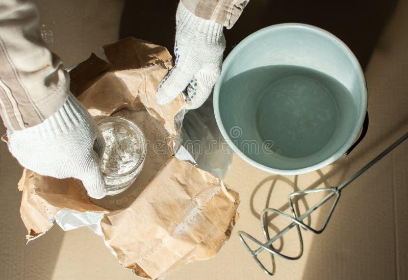 Il costruttore dell'uomo prepara una miscela per mastice fotografia stock