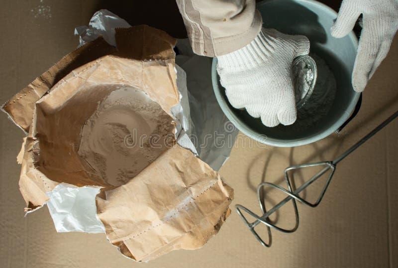 Il costruttore dell'uomo prepara una miscela per mastice immagini stock