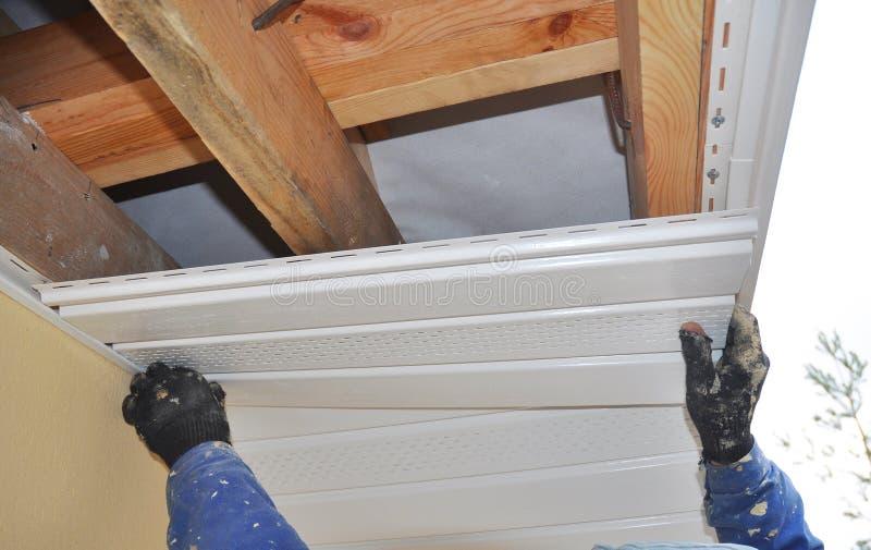 Il costruttore installa l'intradosso Costruzione del tetto Intradosso e fascia fotografia stock libera da diritti