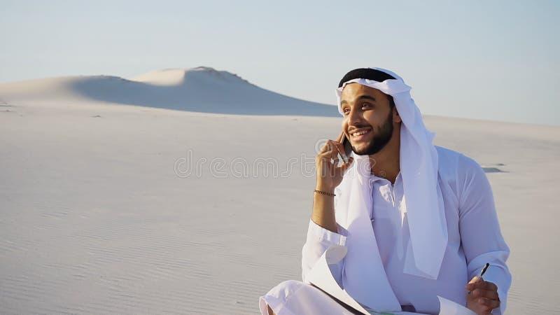 Il costruttore maschio sicuro di sceicco dei UAE dell'Arabo parla su spirito cellulare fotografia stock