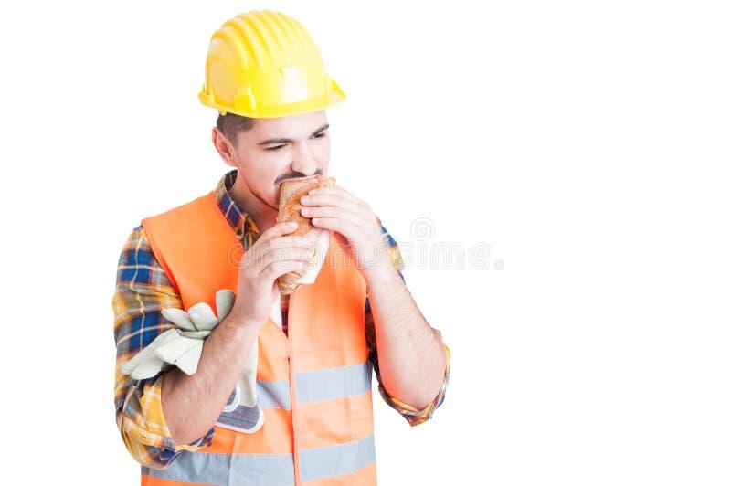Il costruttore maschio sta mangiando un panino saporito nella sua rottura immagine stock libera da diritti