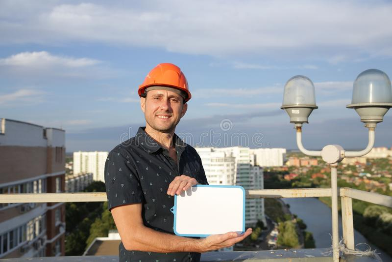 Il costruttore in un casco protettivo con una compressa per la scrittura in sua mano sta stando sul tetto di una costruzione che  fotografia stock