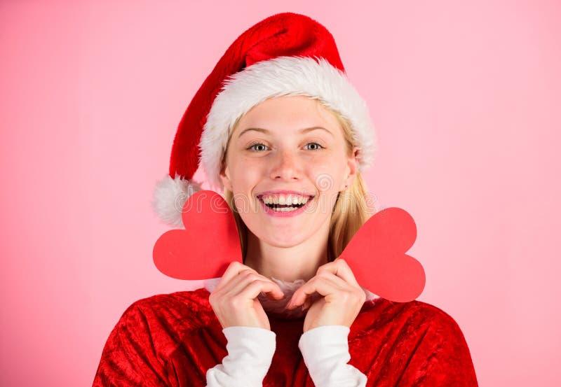 Il costume felice di Santa di usura della ragazza celebra il fondo rosa di natale Buon Natale e buon anno Cuore della tenuta dell fotografia stock libera da diritti