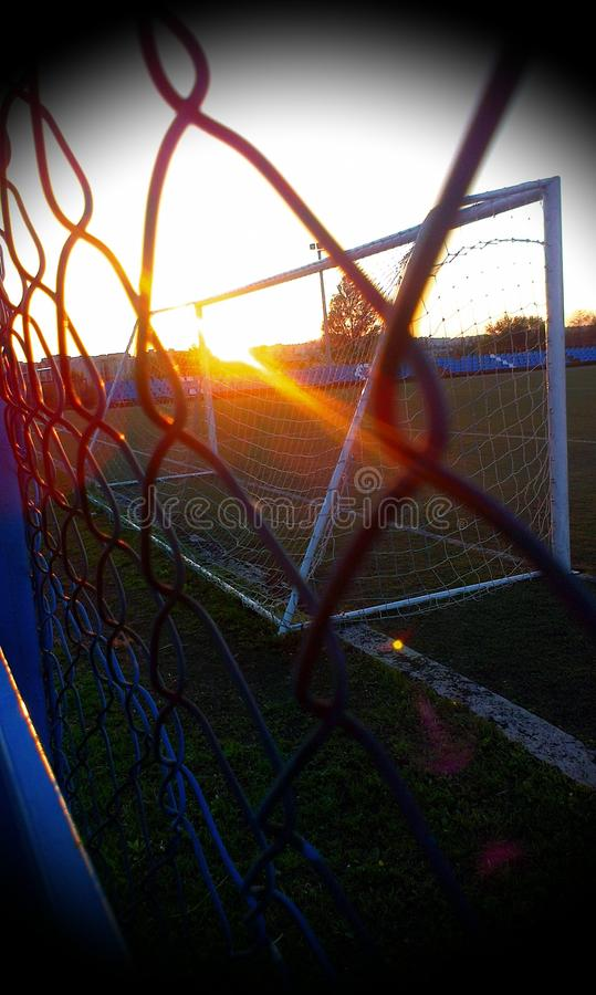 Il coucher du soleil sur le terrain de football photographie stock libre de droits