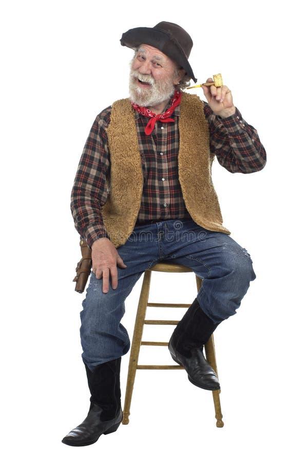 Il cowboy anziano allegro si siede con il tubo della pannocchia di granturco fotografie stock