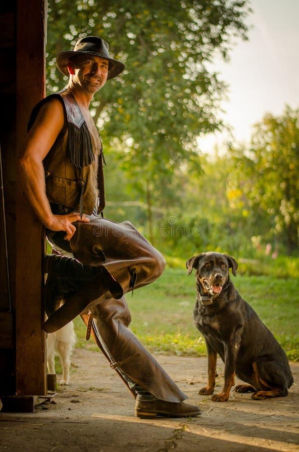 Il cowboy sta con il cane al granaio Un uomo bello con un cappello fotografia stock