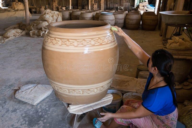 Il craftperson femminile usa la spugna bagnata per definire il modello sul grande vaso di argilla immagini stock