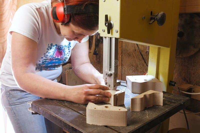 Il Craftswoman sta tagliando un pezzo in lavorazione delle automobili del giocattolo di legno da legno con la sega a nastro immagini stock libere da diritti