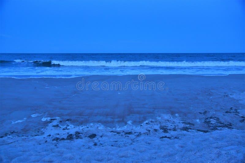 Il crepuscolo comincia a coprire il litorale mentre le onde retrocedono dalla loro alta marea di pomeriggio fotografie stock