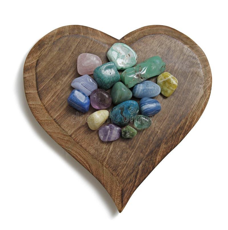 Il cristallo di Chakra ha ruzzolato pietre sulla placca di legno del cuore fotografia stock libera da diritti