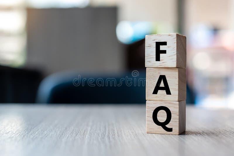 Il cubo di legno con il testo del FAQ ha fatto frequentemente le domande sul fondo della tavola Concetti finanziari, di vendita e immagini stock libere da diritti