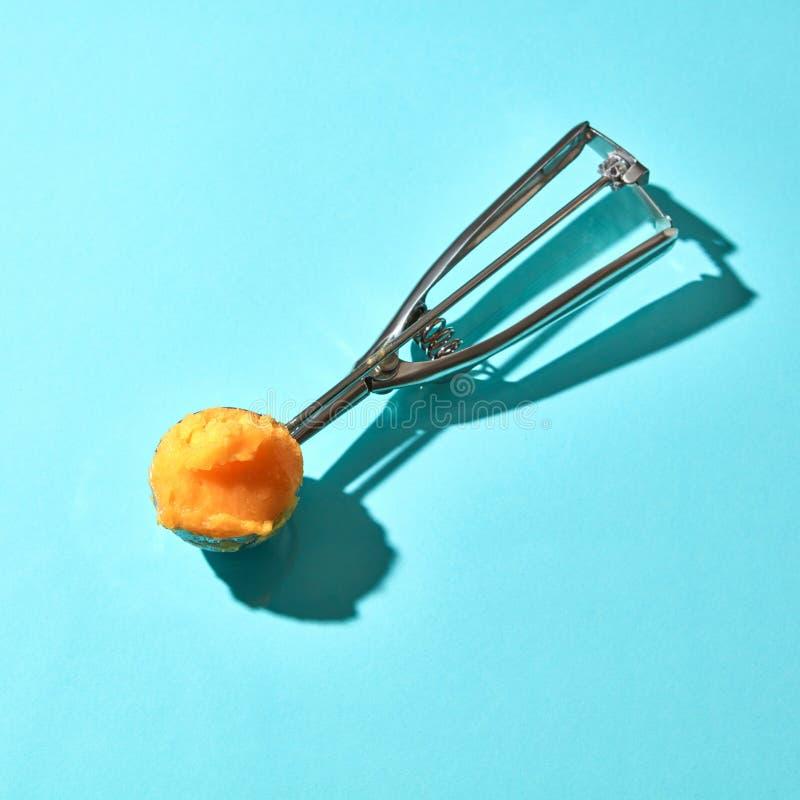 Il cucchiaio per il gelato con il dessert giallo del mango su un fondo blu con le ombre dure immagini stock libere da diritti