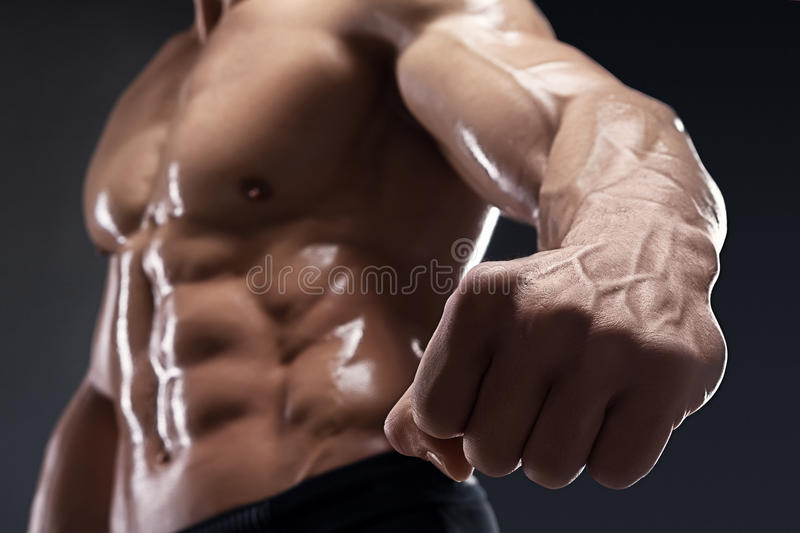 Il culturista muscolare bello mostra il suoi pugno e vena fotografie stock libere da diritti