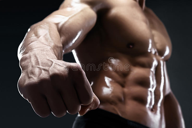 Il culturista muscolare bello mostra il suoi pugno e vena fotografia stock libera da diritti