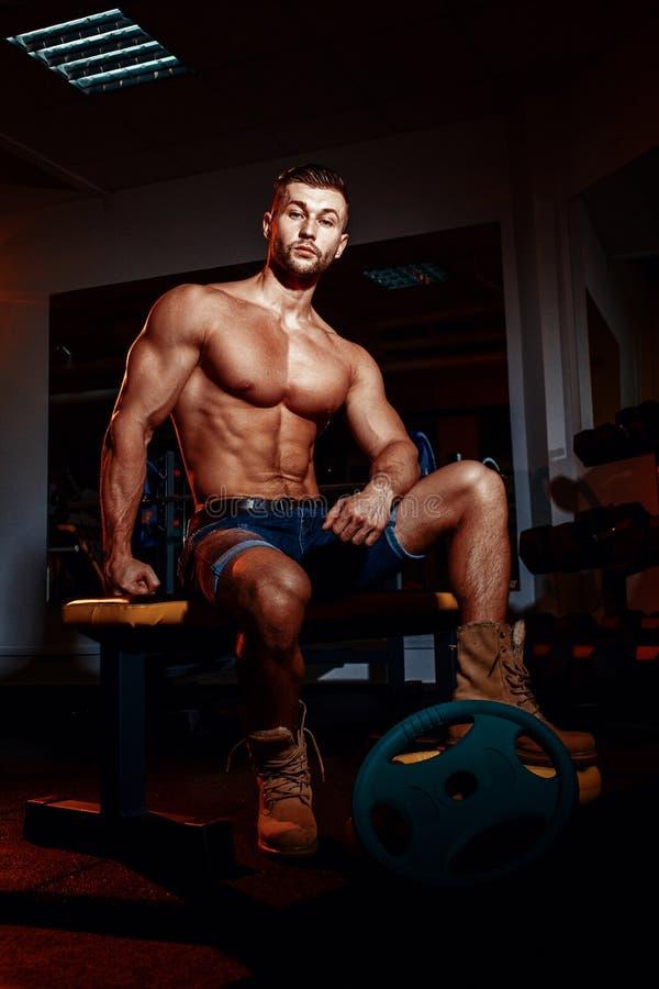 Il culturista si siede su un banco di peso, lui prende una rottura Uomo muscolare ad un posto di allenamento in una palestra e so fotografia stock libera da diritti