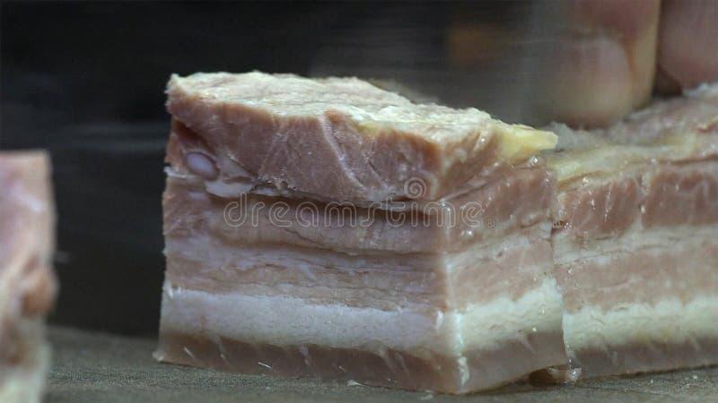 Il cuoco del cuoco unico taglia il grande pezzo di carne di maiale salata sul tagliere di legno con il coltello, fotografie stock