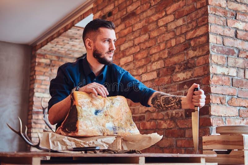Il cuoco del cuoco unico tiene il coltello e la posa vicino ad una tavola con carne a scatti esclusiva in una cucina con l'intern immagini stock
