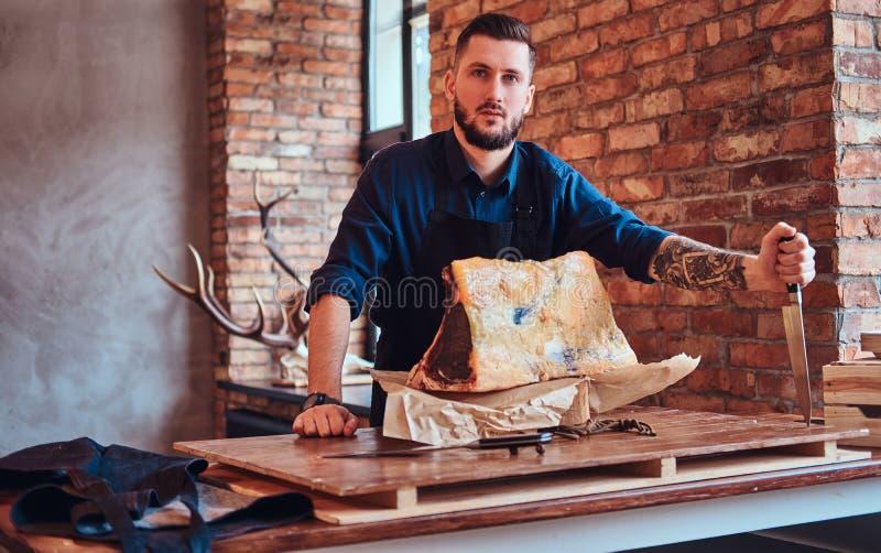 Il cuoco del cuoco unico tiene il coltello e la posa vicino ad una tavola con carne a scatti esclusiva in una cucina con l'intern fotografia stock