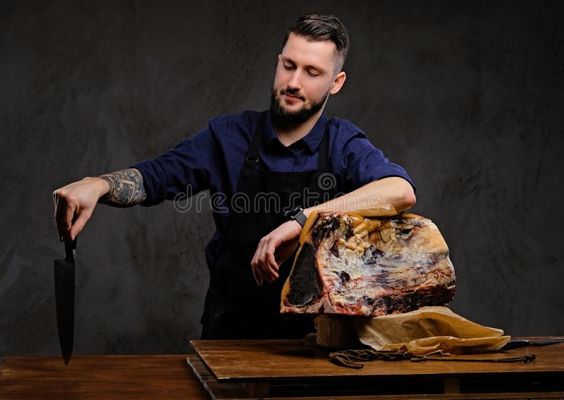 Il cuoco del cuoco unico tiene il coltello e la posa vicino ad una tavola con carne a scatti esclusiva su un fondo scuro fotografia stock libera da diritti