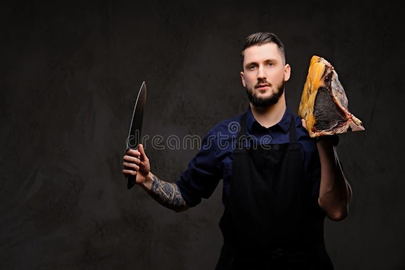 Il cuoco del cuoco unico tiene il coltello ed il grande pezzo di carne curata esclusiva su un fondo scuro immagine stock libera da diritti