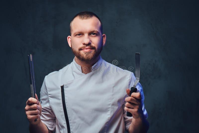 Il cuoco del cuoco unico tiene un coltello sopra fondo grigio scuro immagini stock