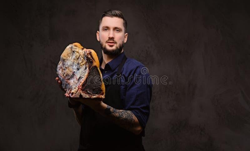 Il cuoco del cuoco unico tiene un grande pezzo di carne curata esclusiva su un fondo scuro fotografie stock