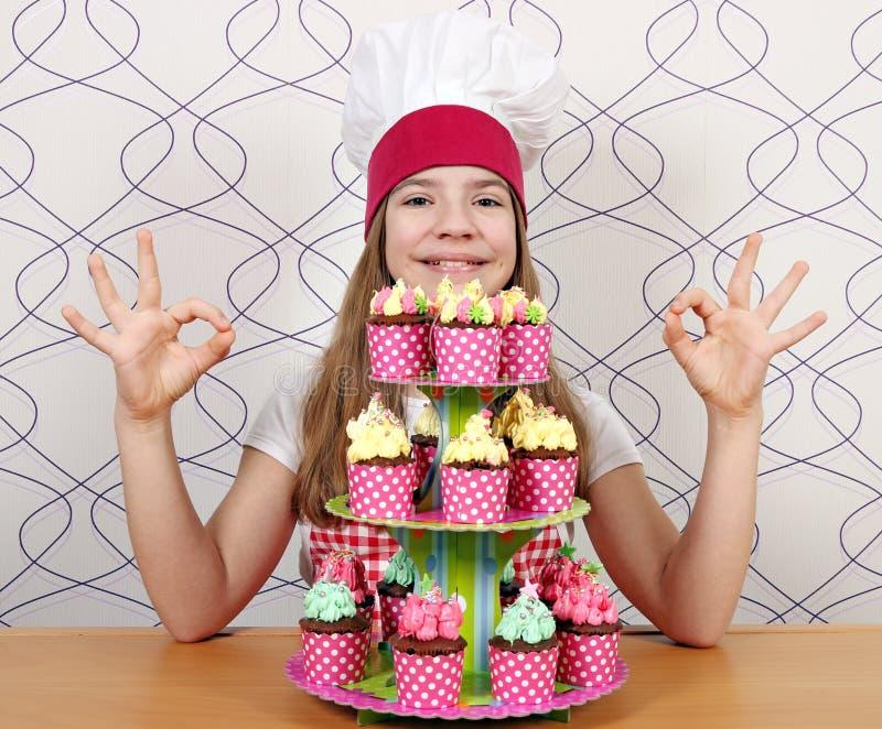 il cuoco della bambina con i muffin e la mano giusta canta fotografie stock