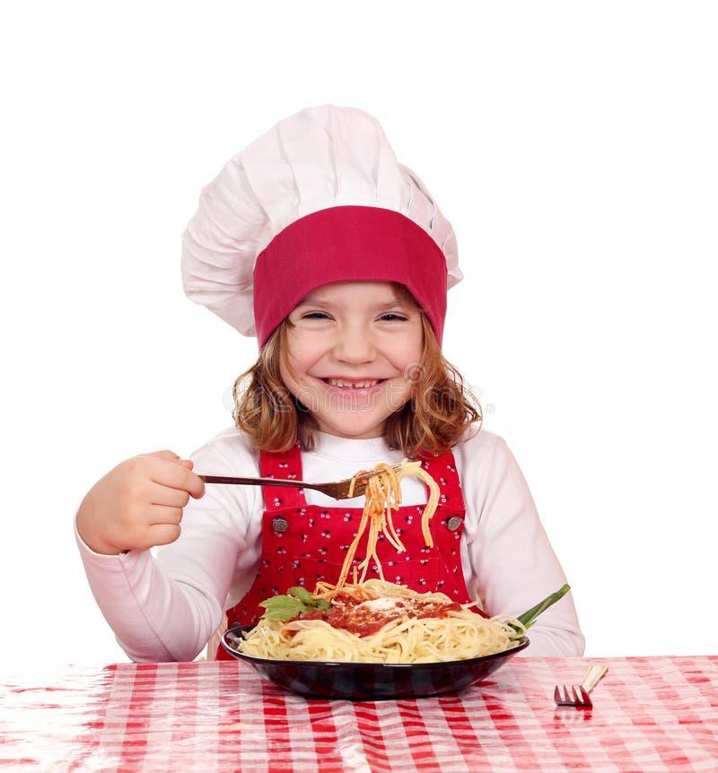 Il cuoco della bambina mangia gli spaghetti fotografie stock