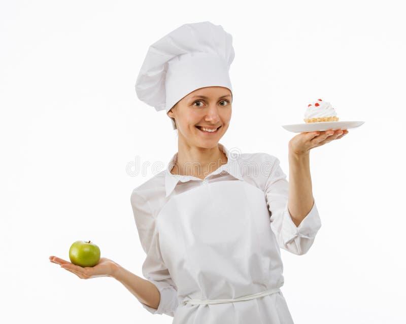 Il cuoco della donna sceglie fra una mela e un dolce fotografia stock