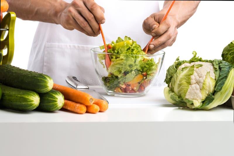 Il cuoco della mano dell'uomo produce a verdure della miscela l'insalata sulla cucina immagini stock libere da diritti