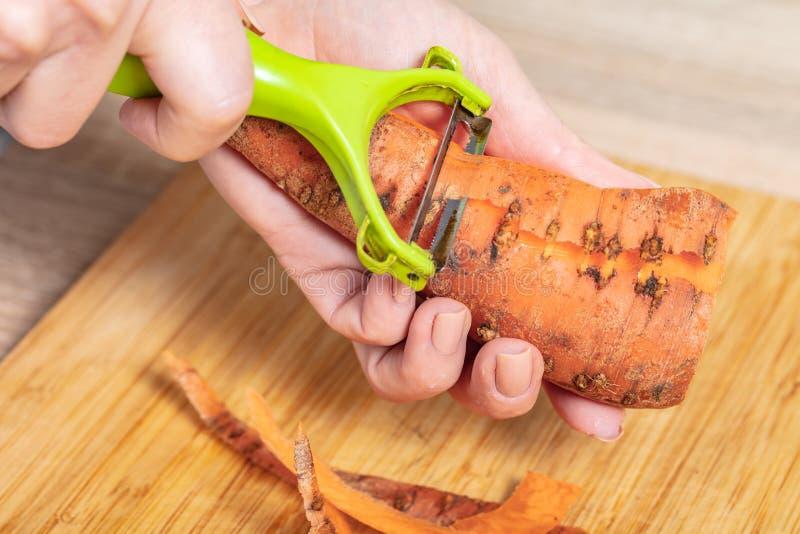 Il cuoco pulisce le carote fotografia stock