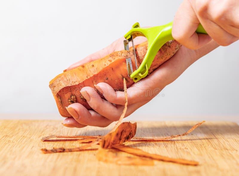 Il cuoco pulisce le carote fotografie stock libere da diritti