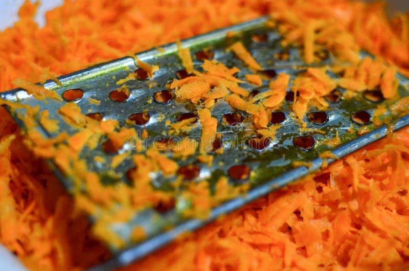 Il cuoco sfrega le carote su una grattugia illustrazione vettoriale