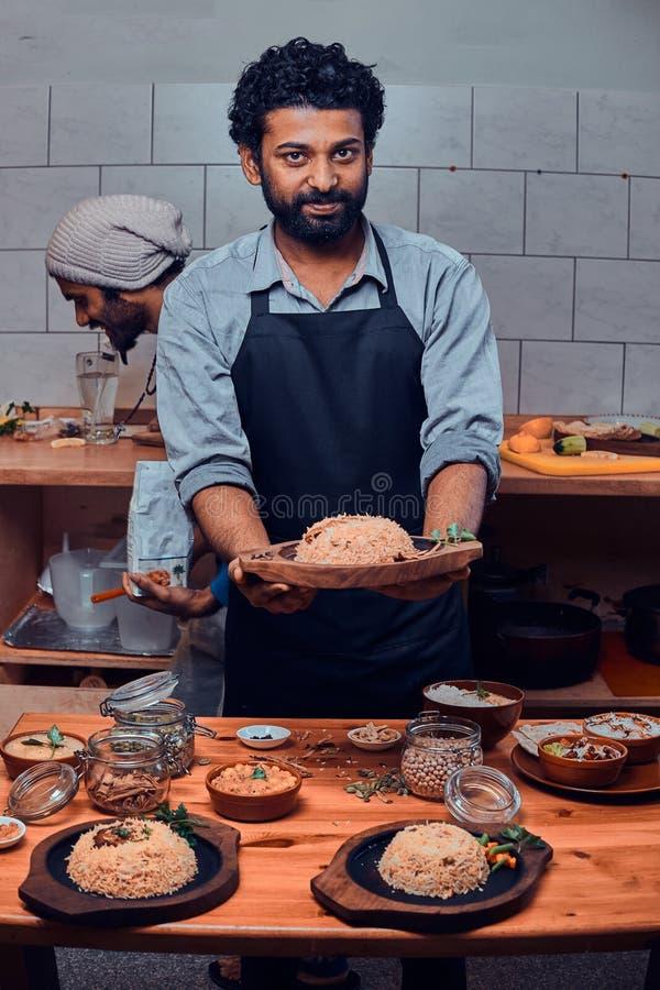 Il cuoco sorridente è piatto di legno del holdind con l'aumento immagini stock libere da diritti