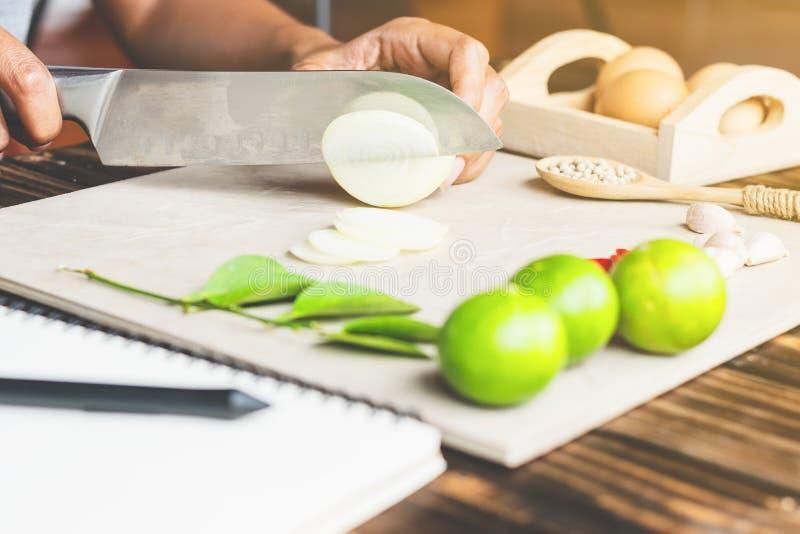 Il cuoco sta tagliando la cipolla a pezzi, tiro del primo piano, affettante fotografia stock libera da diritti
