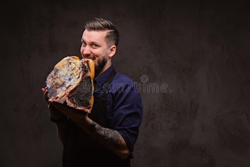 Il cuoco unico affamato morde il grande pezzo di carne curata esclusiva su fondo scuro fotografie stock libere da diritti