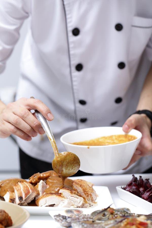 Il cuoco unico applica la minestra di pollo per arrostire la Turchia fotografia stock libera da diritti