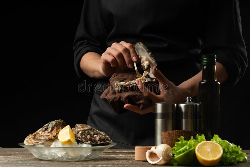 Il cuoco unico apre e pulisce l'ostrica cruda contro lo sfondo di vino bianco, di lattuga, dei limoni e delle limette Con spazio  fotografia stock