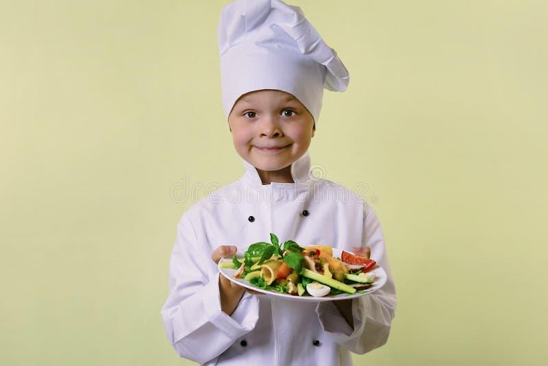 Il cuoco unico divertente del ragazzo ha cucinato l'insalata con le verdure, il formaggio ed il prosciutto immagine stock
