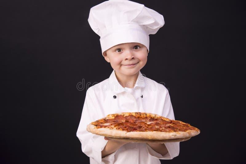 Il cuoco unico divertente tiene il salame della pizza fotografia stock libera da diritti