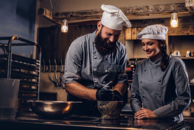 Il cuoco unico frantuma i semi di sesamo in un mortaio per la cottura del pane Cuoco unico che insegna al suo assistente a cuocer fotografia stock