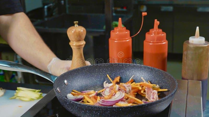 Il cuoco unico frigge le varie verdure e carne con burro su una padella calda fotografia stock libera da diritti