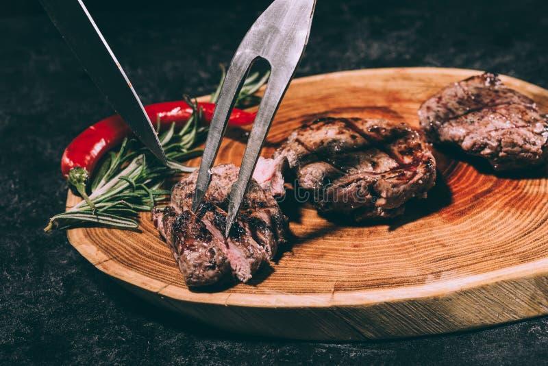 Il cuoco unico in grembiule con la forcella della carne ed il coltello che affetta il buongustaio hanno grigliato le bistecche co immagini stock libere da diritti