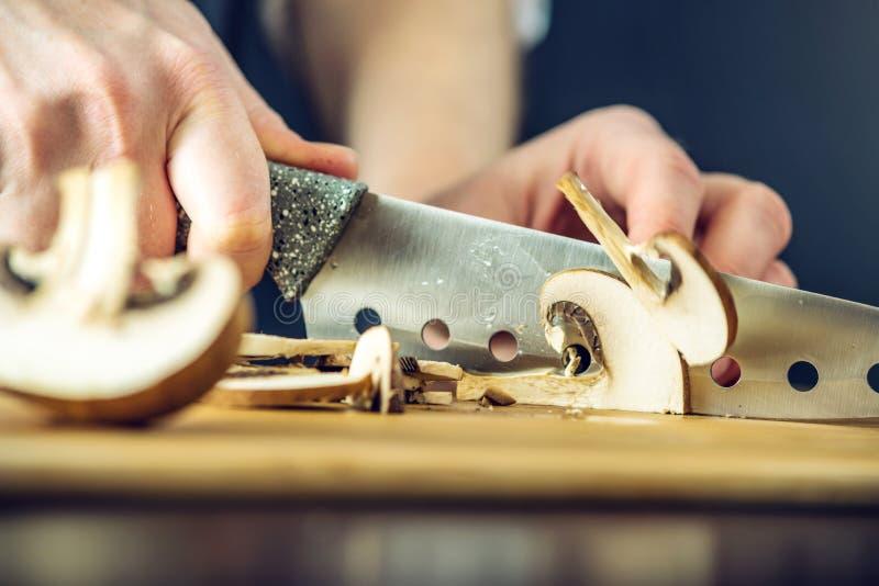 Il cuoco unico in grembiule nero taglia i funghi con un coltello Concetto dei prodotti ecologici per cucinare immagine stock