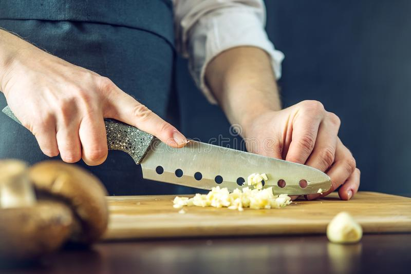 Il cuoco unico in grembiule nero taglia l'aglio con un coltello Concetto dei prodotti ecologici per cucinare immagine stock libera da diritti