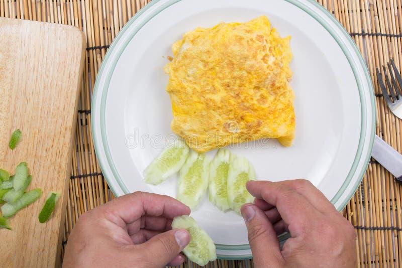 Il cuoco unico ha decorato il bacon infornato del riso con il cetriolo immagini stock