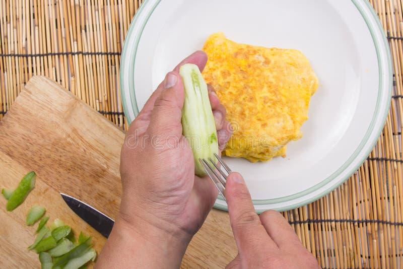 Il cuoco unico ha decorato il bacon infornato del riso con il cetriolo immagine stock