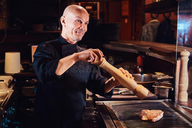 Il cuoco unico matrice che cucina la bistecca di manzo deliziosa su una cucina in un ristorante, pepa la carne con un mulino di p immagine stock libera da diritti