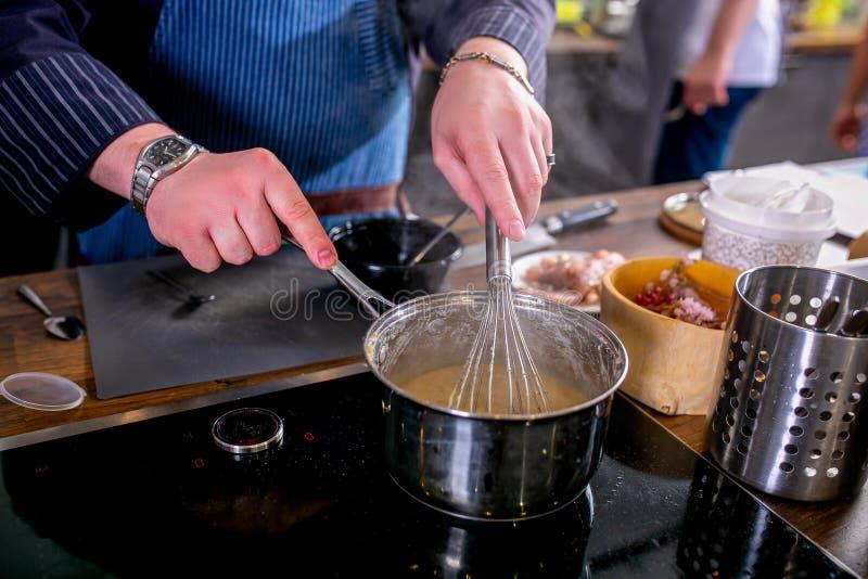 Il cuoco unico mescola la salsa in una casseruola facendo uso del sbatte Classe matrice nella cucina Il processo di cottura Per g fotografia stock
